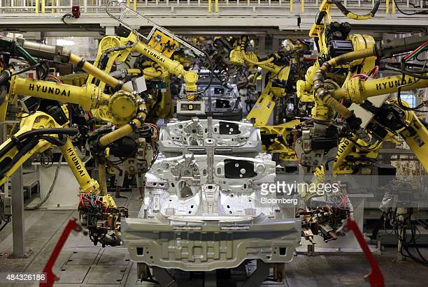 Robotic arms weld body panels to Kia Rio vehicles on the production line at the Hyundai Motors Corp automobile plant in St Petersburg Russia on...