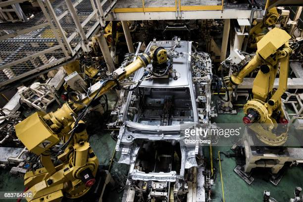 Robotic arms work on the body shells of automobiles on the production line inside the Suzuki Motor Corp plant in Esztergom Hungary on Monday May 15...