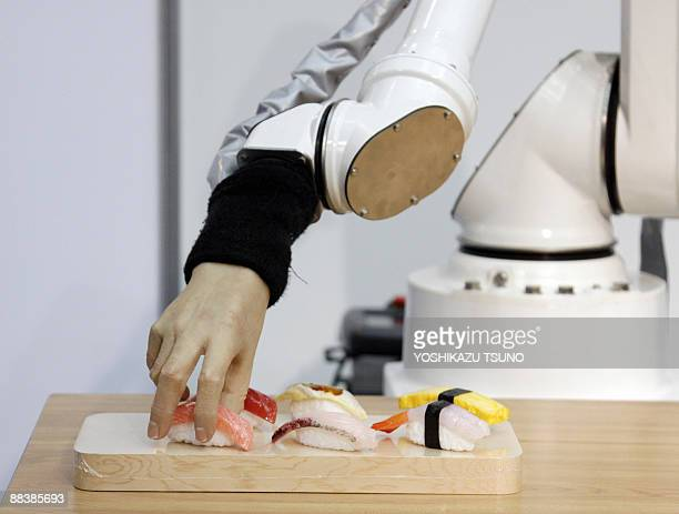 A robotic hand produced by Japanese robotics company Squse picks up a piece of sushi during a demonstration at the International Food Machinery and...