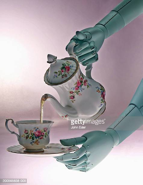 Robotic hands pouring tea from teapot into antique teacup, close-up