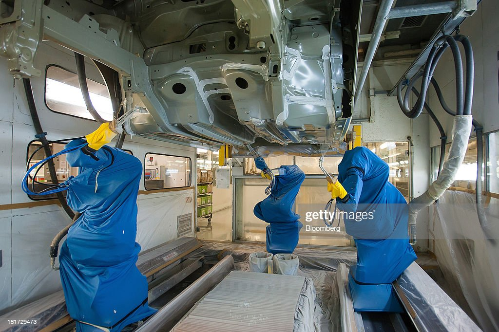 Robotic machines spray the underside of a Peugeot Partner automobile with sealant at the PSA Peugeot Citroen production plant in Mangualde, Portugal, on Monday, Sept. 23, 2013. Some economists point to falling labor costs across southern Europe as a sign the region may be becoming more attractive as a manufacturing base. Photographer: Mario Proenca/Bloomberg via Getty Images
