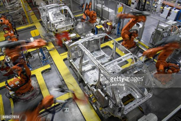 Robotic systems work on the chassis of a car during an automated stage of production at the Jaguar Land Rover factory on March 1 2017 in Solihull...