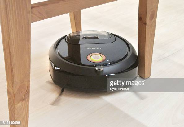 A robotic vacuum cleaner called 'minimaru' developed by Hitachi Appliances Inc cleans the floor under a chair in a demonstration in Tokyo on Oct 17...