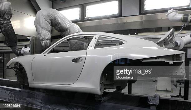 Robots apply paint to the body of a Porsche AG 911 automobile as it travels through the company's new spraying facility in Stuttgart Germany on...