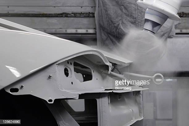 Robots apply paint to the body of a Porsche AG Cayman automobile as it travels through the company's new spraying facility in Stuttgart Germany on...