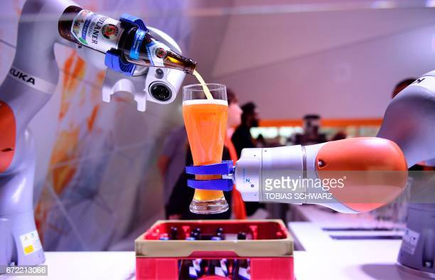 Robots serves beer at the booth of Kuka at the Hanover Fair in Hanover northern Germany on April 24 2017 / AFP PHOTO / TOBIAS SCHWARZ