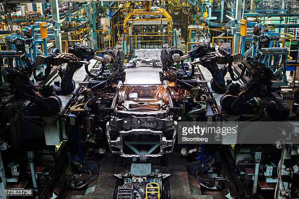 Robots weld the chassis of a Honda Motor Co Amaze vehicle on the production line of the Honda Cars India Ltd plant in Greater Noida India on...