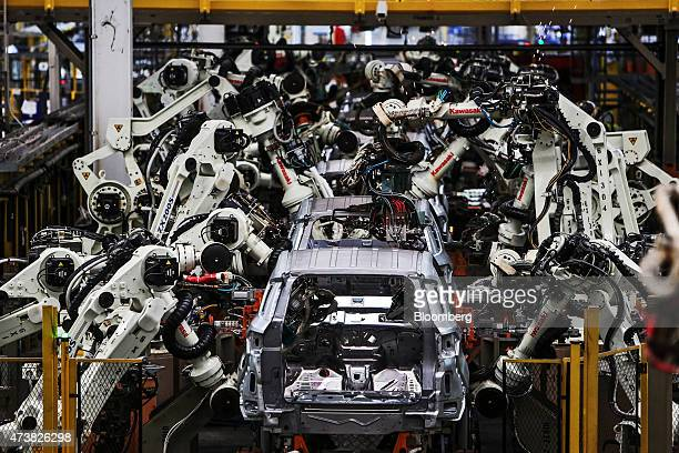 Robots weld vehicle bodies as they move through the body shop station on the production line at the Ford Motor Co factory in Pluak Daeng Rayong...