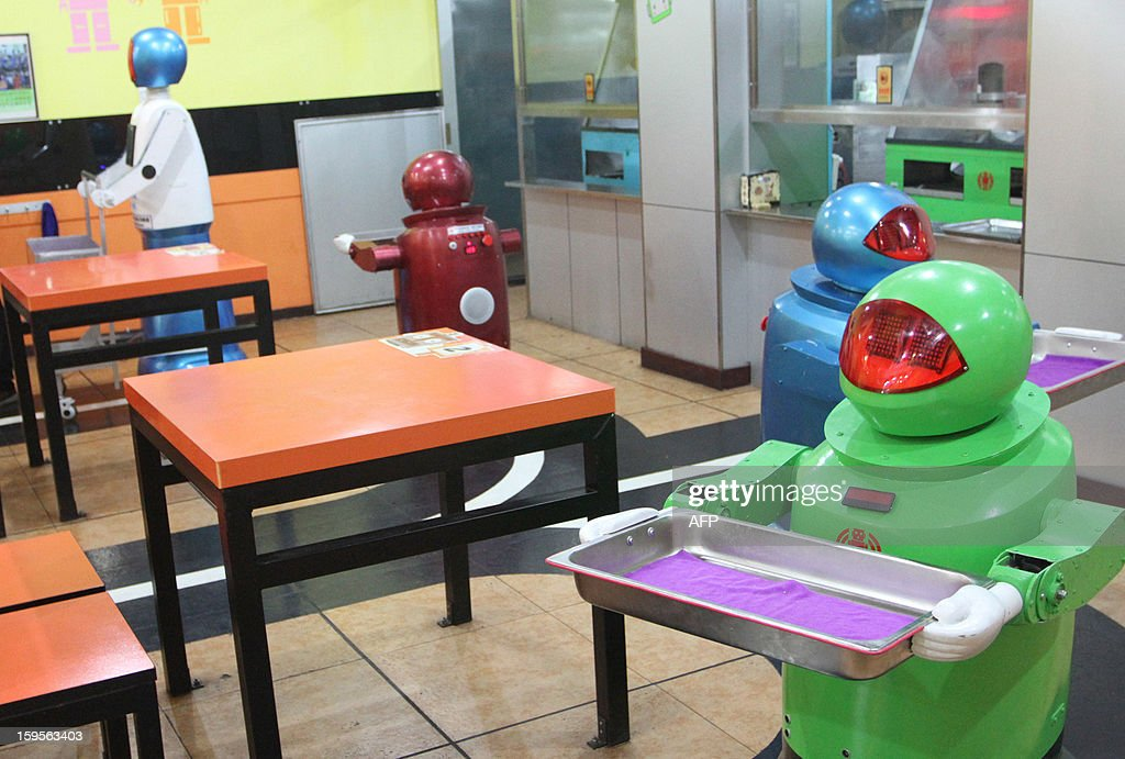 Robots work in a robot-themed restaurant in Harbin, northeast China's Heilongjiang province on January 16, 2013. Twenty robots perform a variety of chores, from ushering in guests to waiting tables and cooking dishes. CHINA