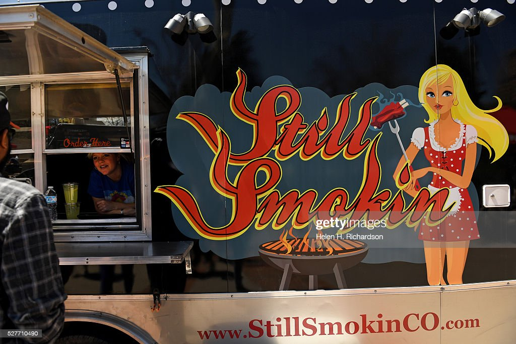 Robyn Gray, left, serves people delicious southern inspired fusion BBQ food from Still Smokin' Food truck at Civic Center Park on the first day of the 11th annual Civic Center EATS on May 3, 2016 in Denver, Colorado. This is metro Denver's largest gathering of gourmet food trucks and carts and is a showcase of Denver's culinary and entrepreneurial diversity. The daily food truck lunch event runs through October 6th from 11 am to 2 pm Tuesdays, Wednesdays and Thursdays.