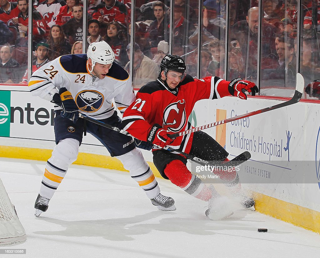 <a gi-track='captionPersonalityLinkClicked' href=/galleries/search?phrase=Robyn+Regehr&family=editorial&specificpeople=171828 ng-click='$event.stopPropagation()'>Robyn Regehr</a> #24 of the Buffalo Sabres and <a gi-track='captionPersonalityLinkClicked' href=/galleries/search?phrase=Andrei+Loktionov&family=editorial&specificpeople=5370946 ng-click='$event.stopPropagation()'>Andrei Loktionov</a> #21 of the New Jersey Devils battle for control of the puck during the game at the Prudential Center on March 7, 2013 in Newark, New Jersey.