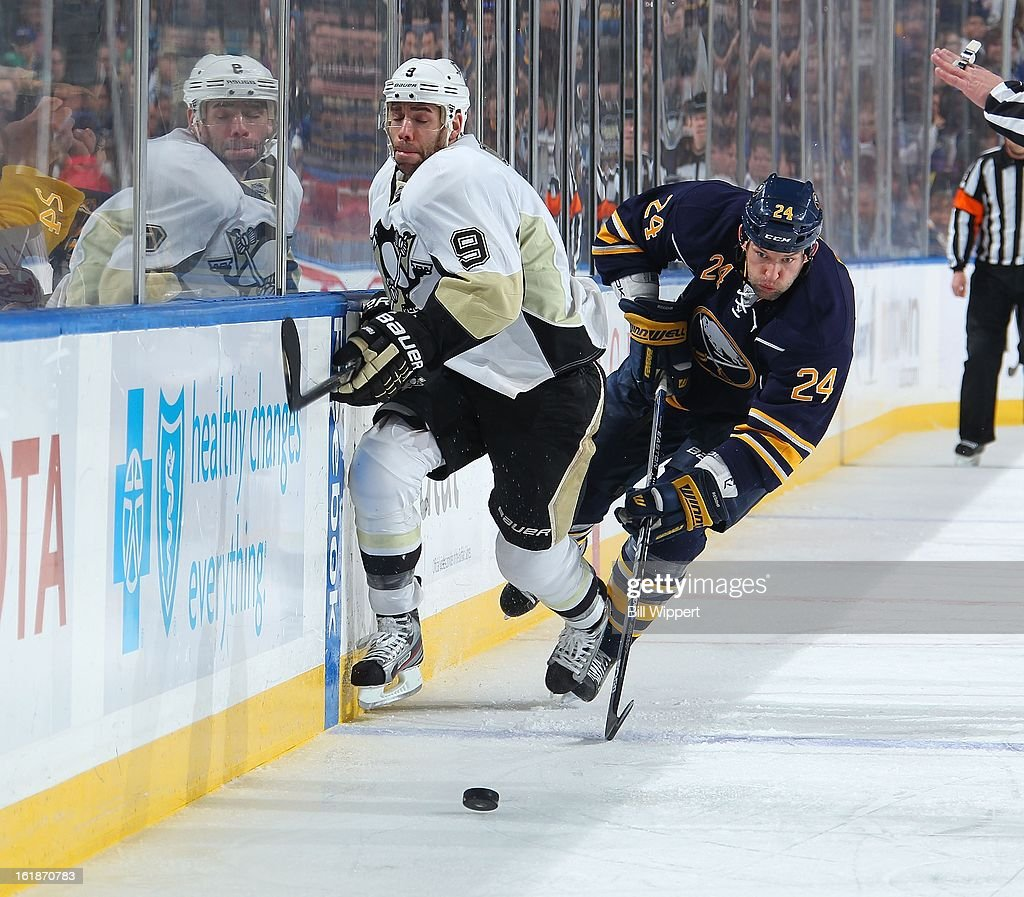 Robyn Regehr #24 of the Buffalo Sabres chases after the puck against Pascal Dupuis #9 of the Pittsburgh Penguins on February 17, 2013 at the First Niagara Center in Buffalo, New York.