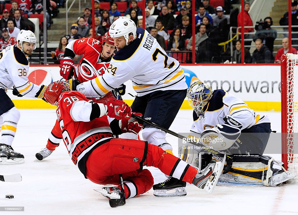 <a gi-track='captionPersonalityLinkClicked' href=/galleries/search?phrase=Robyn+Regehr&family=editorial&specificpeople=171828 ng-click='$event.stopPropagation()'>Robyn Regehr</a> #24 of the Buffalo Sabres separates <a gi-track='captionPersonalityLinkClicked' href=/galleries/search?phrase=Jussi+Jokinen&family=editorial&specificpeople=570599 ng-click='$event.stopPropagation()'>Jussi Jokinen</a> #36 of the Carolina Hurricanes from the puck as he drives to the net during play at PNC Arena on January 24, 2013 in Raleigh, North Carolina. Carolina defeated Buffalo, 6-3.