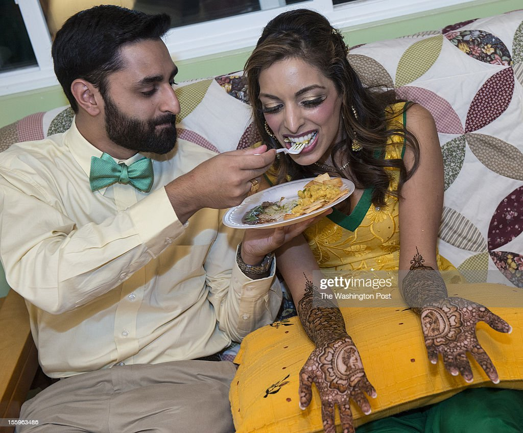 RobyThomas, 26, feeds his bride-to-be Ashley Singh, 26, as she waits for her bridal mednhi to dry Wednesday October 3, 2012 in Fairfax Station, VA.