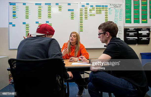 Roca case workers Sulai Rosa center and Matthew Swoveland right talk with a young man who is hoping to change his class schedule at Roca in Chelsea...
