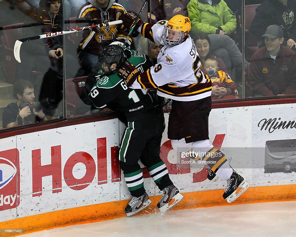 Rocco Grimaldi #19 of North Dakota is taken into the boards by Nate Schmidt #29 of Minnesota January 19, 2013 at Mariucci Arena in Minneapolis, Minnesota.