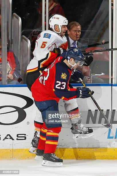Rocco Grimaldi of the Florida Panthers checks Mark Giordano of the Calgary Flames into the boards at the BBT Center on November 8 2014 in Sunrise...