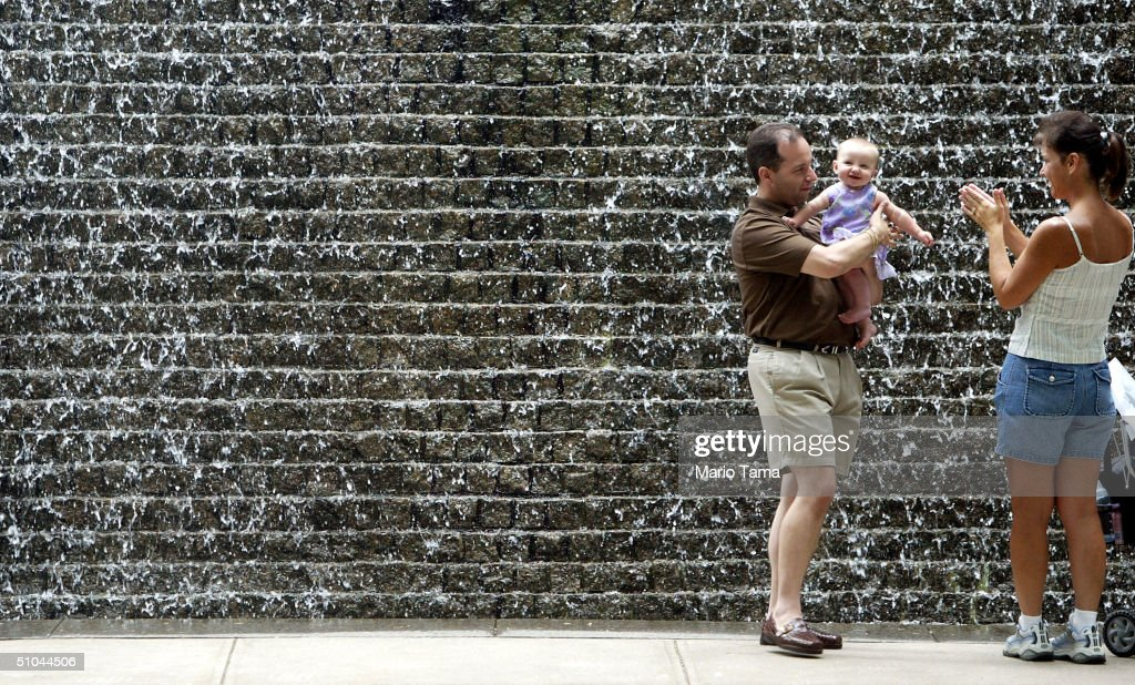 Rocco Moraglia holds his daughter Jenna 7 months as mother Carla looks on during & Wall Street Opens Its Doors On Community Day Photos and Images ... pezcame.com