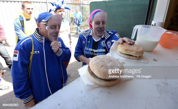 Rochdale fans wearing face masks of manager Keith Hill queue for a burger inside the stadium before the Sky Bet League Two match at Rodney Parade...