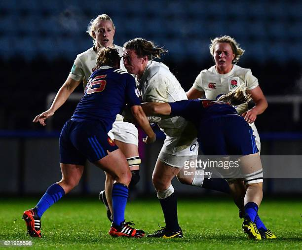 Rochelle Clark of England is tackled by Gaelle Mignot and Romane Menager of France during the Old Mutual Wealth Series match between England Women...