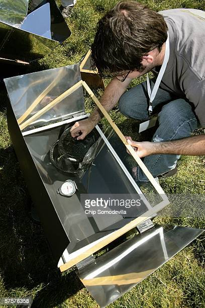 Rochester Institute of Technology Industrial and Systems Engineering student Christopher Wood puts a small pot inside a solarpowered oven at the...