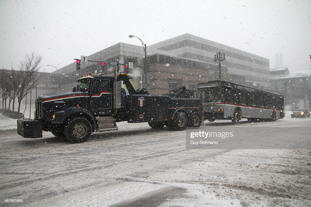 A Rochester-Genesee Regional Transportation Authority truck tows a disabled passenger bus back to the garage during a snow storm on February 5, 2014 in Rochester, New York. An additional foot of snow blanketed Western New York overnight in the latest winter storm system that has affected areas from Kansas to Maine.