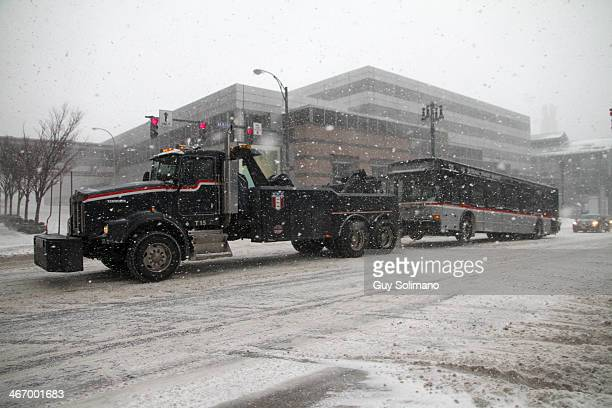 RochesterGenesee Regional Transportation Authority truck tows a disabled passenger bus back to the garage during a snow storm on February 5 2014 in...