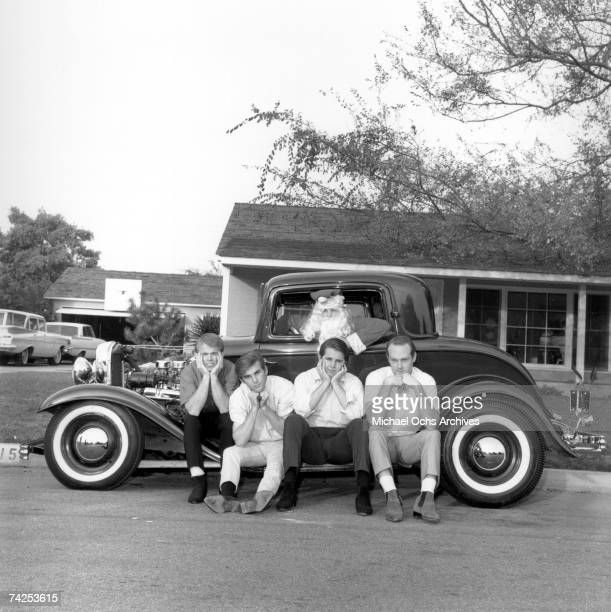 Rock and roll band 'The Beach Boys' pose for a portrait in front of a vintage car with Brian Wilson in a Santa suit Al Jardine Dennis Wilson Carl...