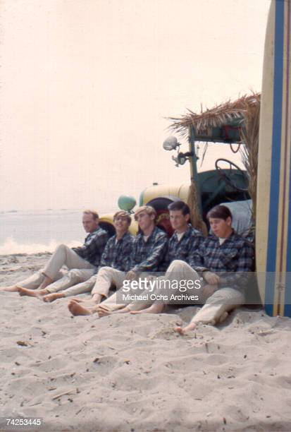Rock and roll band 'The Beach Boys' pose for a portrait with a vintage station wagon in August 1962 in Los Angeles California Mike Love David Marks...