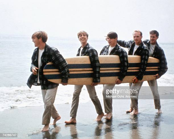 Rock and roll band 'The Beach Boys' walk along the beach holding a surfboard for a portrait session in August 1962 in Los Angeles California Dennis...
