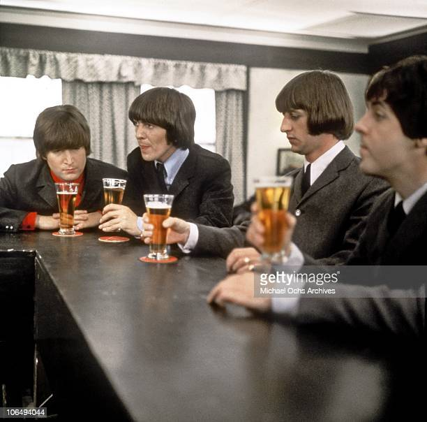 Rock and roll band 'The Beatles' drink a beer in a still from their movie 'Help' which was released in 1965 John Lennon George Harrison Ringo Starr...