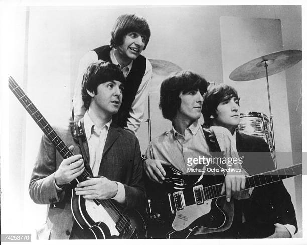 Rock and roll band 'The Beatles' pose for a portrait holding their instruments in circa 1965