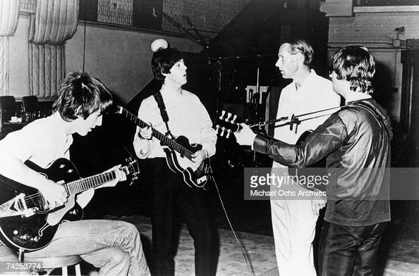 Rock and roll band 'The Beatles' pose for a portrait in the studio with their producer George Martin in cicra 1964 George Harrison Paul McCartney...