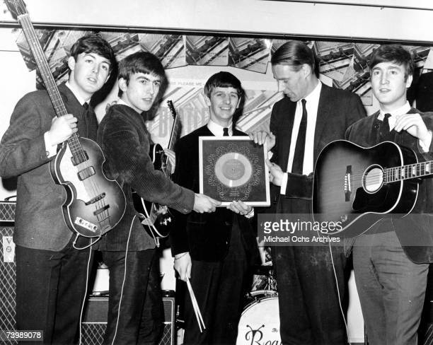 Rock and roll band 'The Beatles' poses for a portrait with their producer George Martin Paul McCartney George Harrison Ringo Starr producer George...