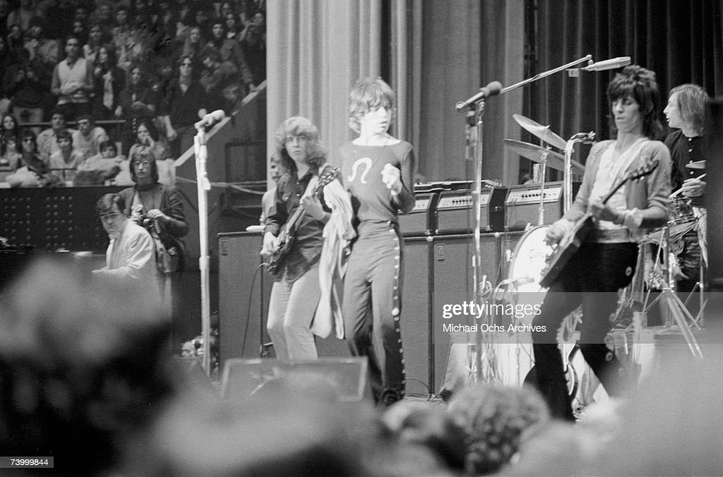 Rock and roll band 'The Rolling Stones' perform onstage as photographer Annie Liebovitz looks on at Madison Square Garden in a concert that was...
