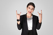 Rock and roll! Businesswoman showing rock sign. Studio shot, indoor. Isolated on grey background