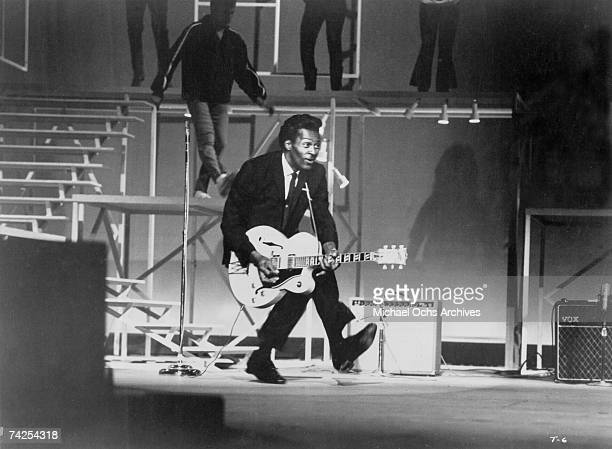 Rock and roll guitarist Chuck Berry performs his 'duck walk' as he plays his electric hollowbody guitar at the TAMI Show on December 29 1964 at the...