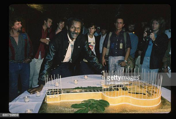Rock and roll legend Chuck Berry stands behind a large guitarshaped birthday cake at a celebration of his 60th birthday