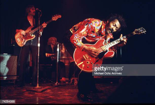 Rock and roll musician Chuck Berry performs onstage with a Gibson hollowbody electric guitar with a bass player and piano player in circa 1970