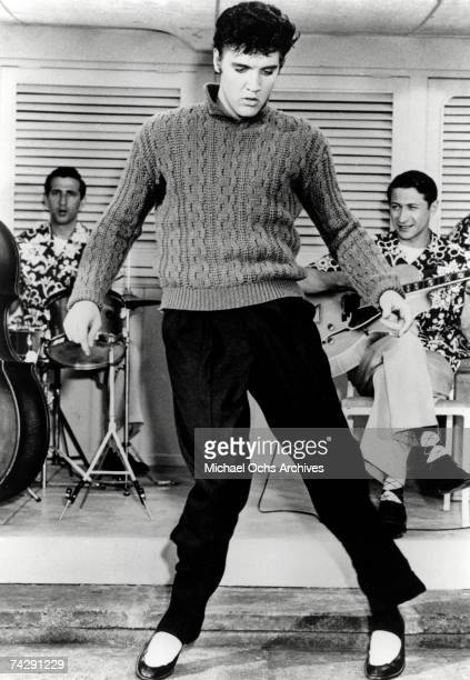 Rock and roll musician Elvis Presley dances in front of his band in a movie still from 1956