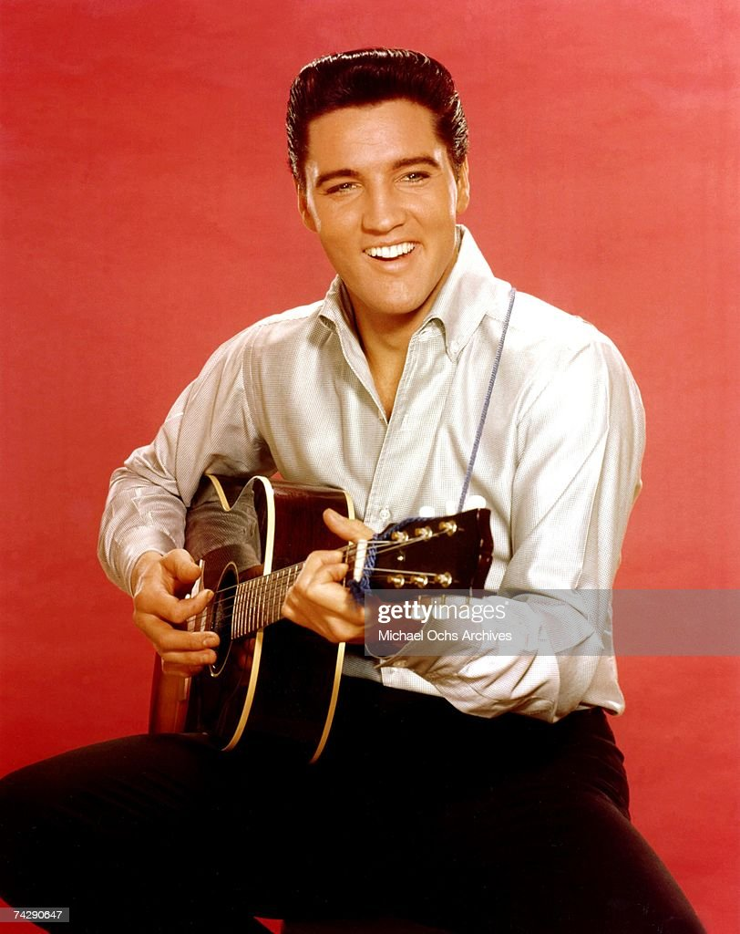 Rock and roll musician Elvis Presley strums an acoustic guitar while posing for a portrait in September 1962 in Culver City California at MGM Studios