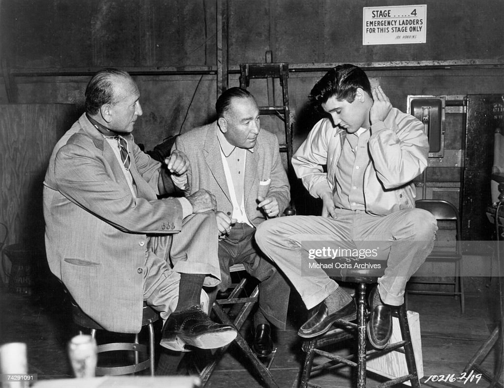 Rock and roll singer Elvis Presley confers with 2 men behind the scenes at a movie set talking to fans in 1960 in Hollywood, California.