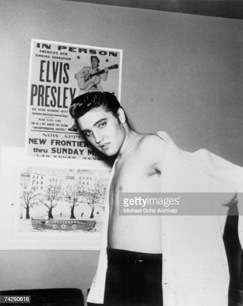 Rock and roll singer Elvis Presley in front of a concert poster with his shirt half on at the New Frontier Hotel on April 23 1956 in Las Vegas Nevada