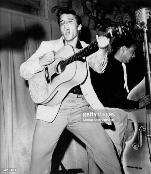 Rock and roll singer Elvis Presley performs on stage with his brand new Martin D28 acoustic guitar on July 31 1955 at Fort Homer Hesterly Armory in...