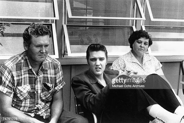 Rock and roll singer Elvis Presley relaxes with his parents Vernon and Gladys in 1956