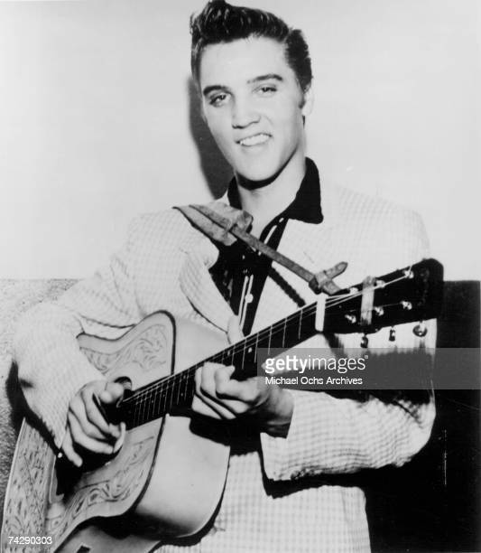 Rock and roll singer Elvis Presley strums his acoustic guitar in a portrait in 1956