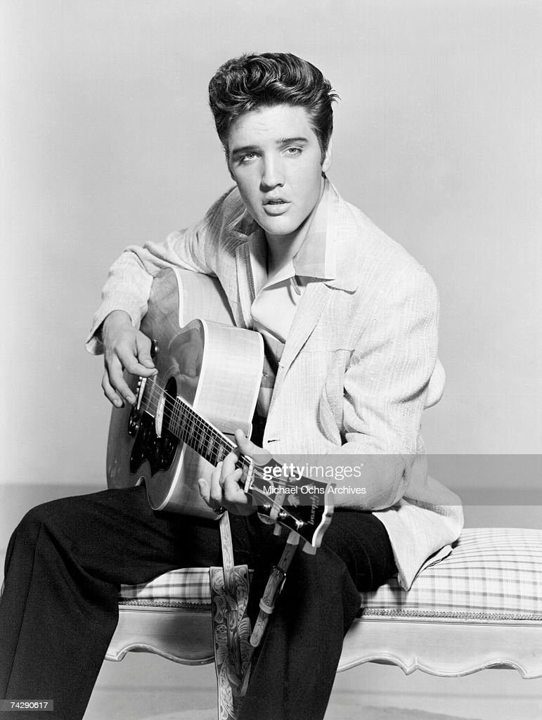 Rock and roll singer <a gi-track='captionPersonalityLinkClicked' href=/galleries/search?phrase=Elvis+Presley&family=editorial&specificpeople=67209 ng-click='$event.stopPropagation()'>Elvis Presley</a> strums his acoustic guitar in a portrait in 1956.