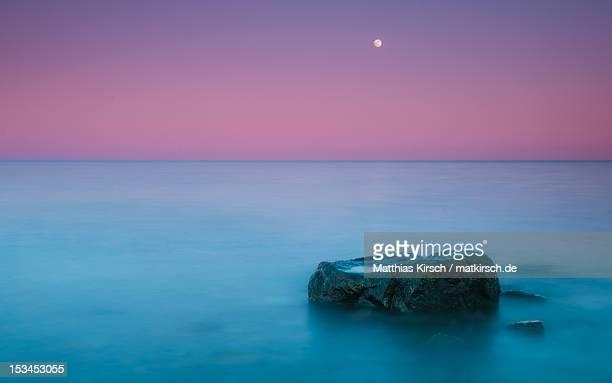 Rock at coast with rising moon