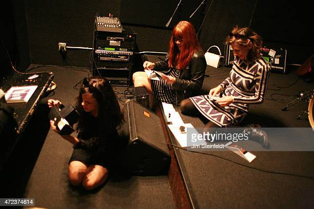 Rock band Babes in Toyland Kat Bjelland Lori Barbero and Maureen Herman review old photos at Amp Rehearsal in N Hollywood California on November 16...