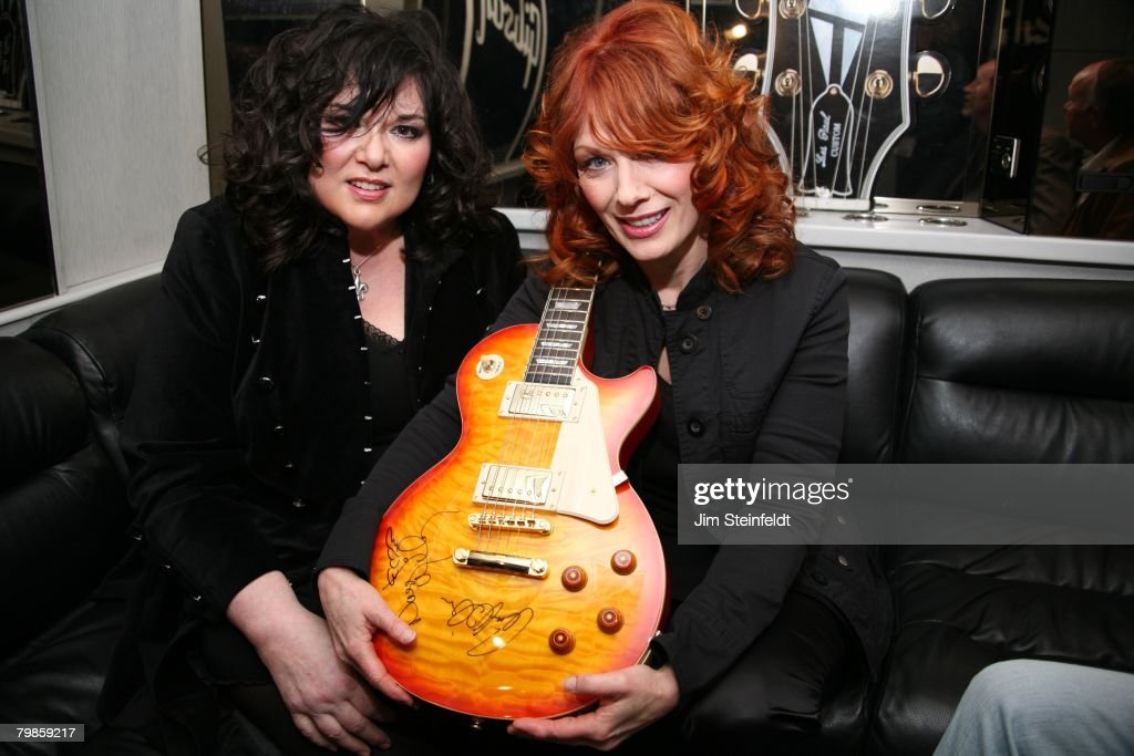 Rock band Heart pose for a portrait in the Gibson tour bus holding an Epiphone Les Paul guitar they have autographed Anaheim California at the NAMM...